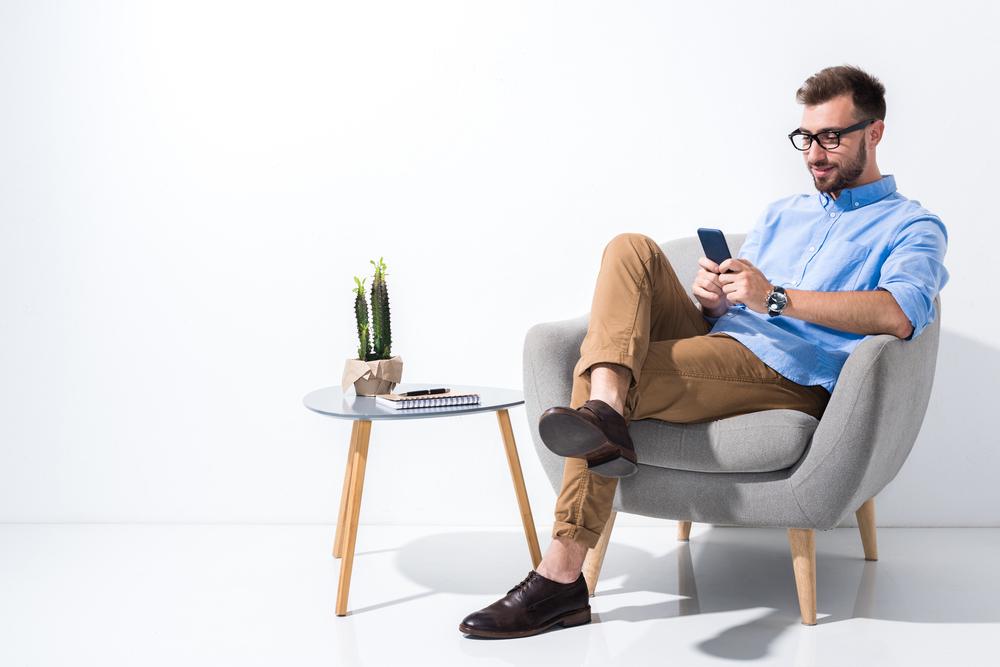 Mann sitzend mit Smartphone